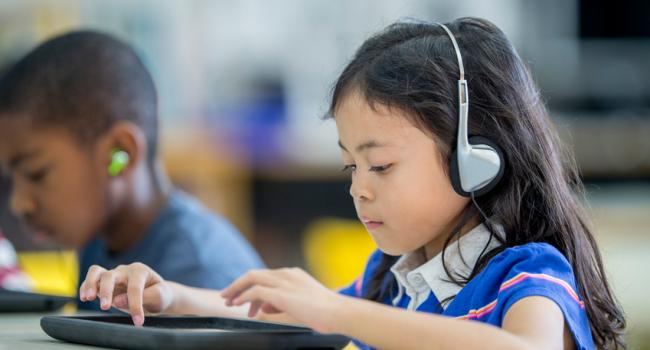 A young girl wearing headphones and using a tablet computer