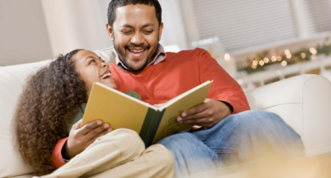 a smiling man and smiling girl looking at a book
