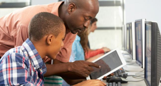 a man looking at a tablet computer with a young boy
