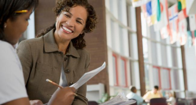 a woman smiling at a young adult who is holding a paper and pencil