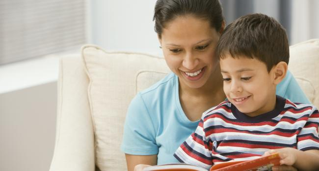 a woman reading to a boy in her lap