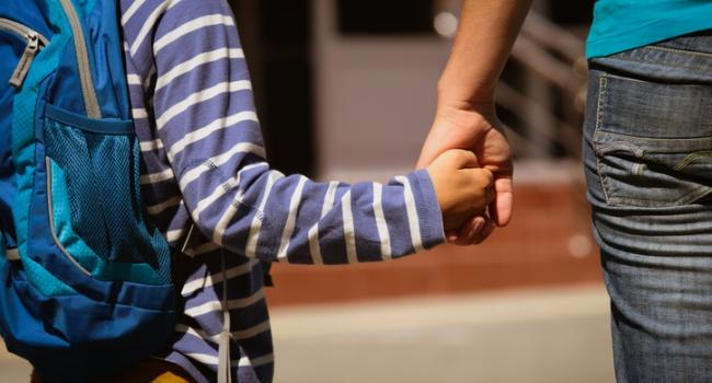 a child wearing a backback holding an adult's hand