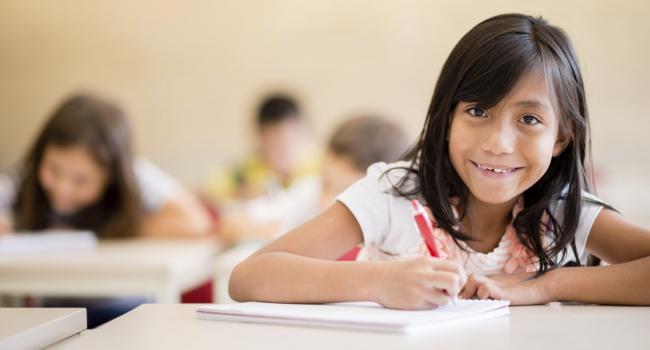 girl smiling at camera while she writes