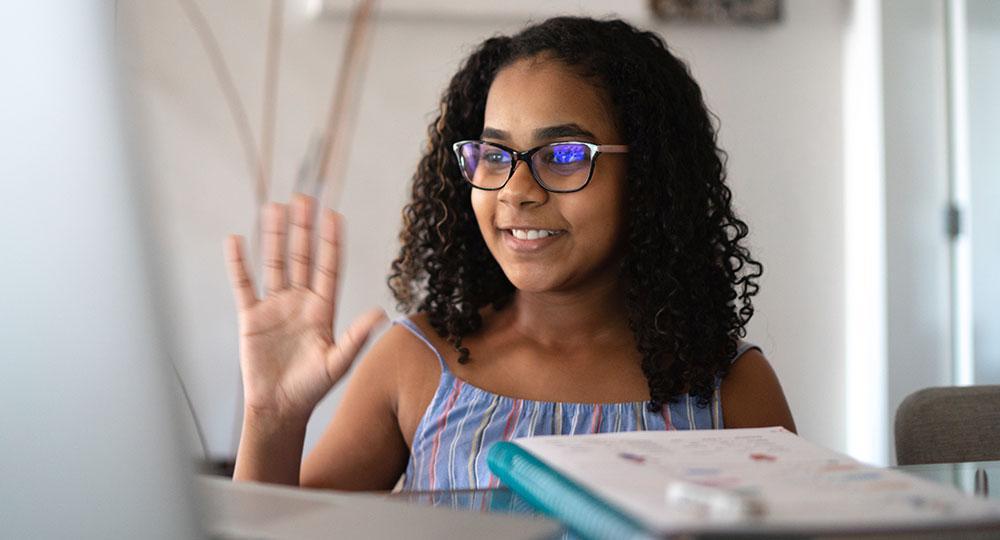 Girl waving at the computer