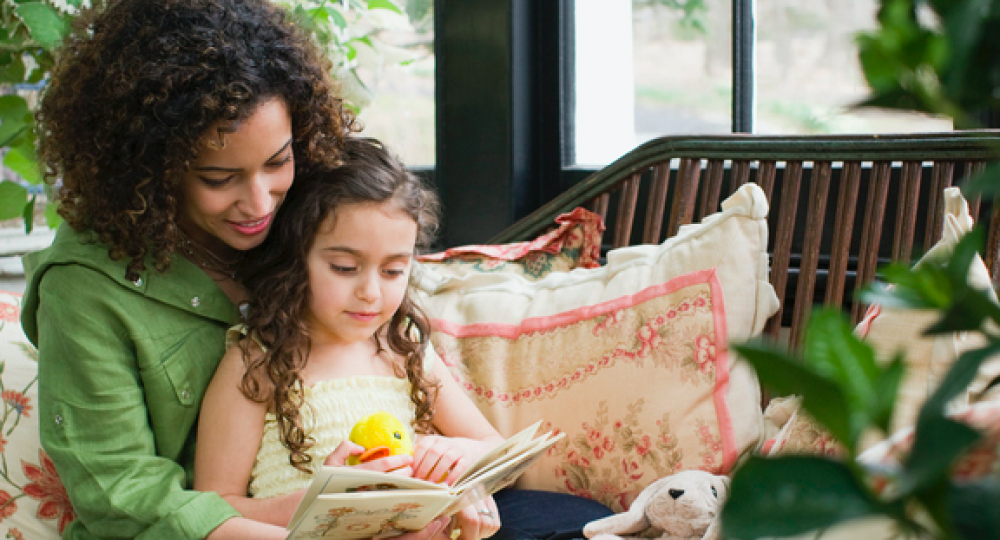 Mom and daughter reading on couch in front of window
