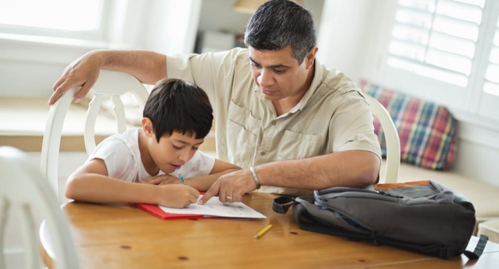 Father helping won with homework at title