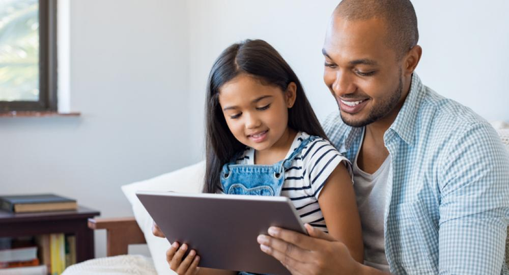 Father and daughter looking at tablet
